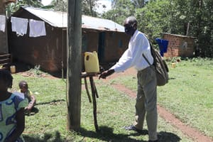 The Water Project: Muraka Community, Peter Itevete Spring -  An Elder Uses An Installed Leaky Tin In The Community