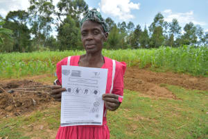 The Water Project: Mungaha B Community, Maria Spring -  Ms Maria Holding Up A Manual