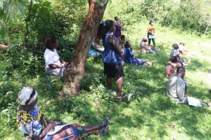 The Water Project: Isembe Community, Amwayi Spring -  A Community Memeber Reading Out The Points From The Chart
