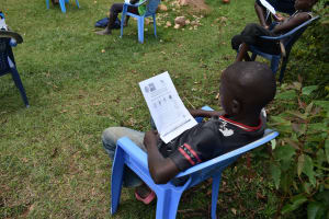 The Water Project: Emaka Community, Ateka Spring -  A Boy Reading Through The Pamphlet