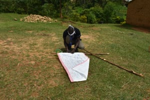 The Water Project: Emaka Community, Ateka Spring -  Mr Wagaka Mounting The Chart On The Support Poles