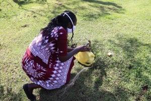 The Water Project: Koloch Community, Solomon Pendi Spring -  Facilitator Fabricates A Jerrycan To Make A Handwashing Leaky Tin