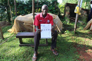 The Water Project: Koitabut Community, Henry Kichwen Spring -  An Elder With The Covid Informational Pamphlet