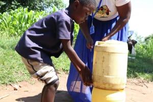 The Water Project: Bukhakunga Community, Khayati Spring -  Using An Improvised Handwashing Station In The Community