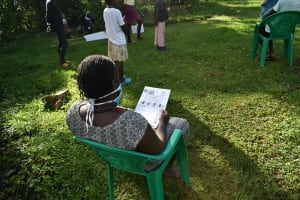 The Water Project: Mukoko Community, Mukoko Spring -  A Community Member Reading Through The Manual