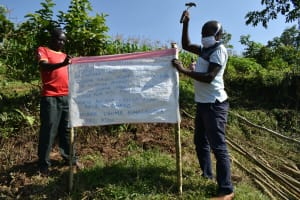 The Water Project: Musango Community, Mwichinga Spring -  Installing Reminder Charts At The Spring