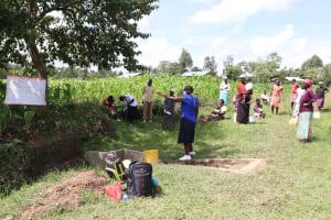 The Water Project: Mukhuyu Community, Kwawanzala Spring -  The Facilitator Leading Using The Chart At Kwawanzala Spring