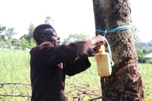 The Water Project: Mukhuyu Community, Kwakhalakayi Spring -  The Chairperson Mounting The Handwashing Station To A Tree At The Entrance Of His Compound