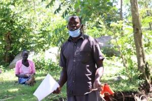 The Water Project: Imbinga Community, Arunga Spring -  A Community Health Volunteer Showcasing Wrong Ways Of Wearing Masks