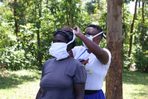 The Water Project: Imbinga Community, Arunga Spring -  Jacky Demonstrates By Helping A Community Member Tie Her Mask Properly
