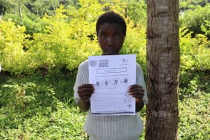 The Water Project: Mubinga Community, Mulutondo Spring -  Holding A Handout With Covid Information