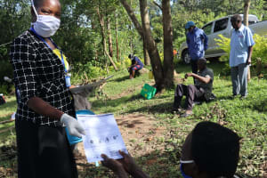 The Water Project: Mubinga Community, Mulutondo Spring -  Issuing Handouts With Covid Information To Participants
