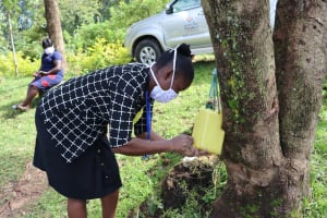 The Water Project: Mubinga Community, Mulutondo Spring -  Mrs Masinde Demonstrating How To Make A Leaky Tin To Community Members At Mulutondo Spring