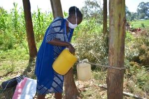 The Water Project: Maondo Community, Ambundo Spring -  Ms Shigali Filling The Handwashing Station With Water