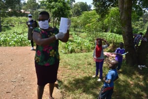 The Water Project: Lutonyi Community, Lutomia Spring -  The Facilitator Demonstrating How To Make A Mask
