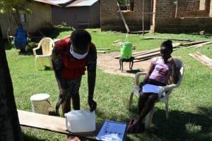 The Water Project: Imbinga Community, Imbinga Spring -  Demonstration Of Making A Leaky Tin Handwashing Station