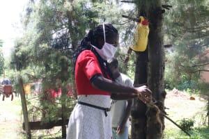 The Water Project: Mukangu Community, Metah Spring -  Handwashing Demonstration Using Leaky Tins