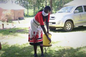 The Water Project: Mukangu Community, Metah Spring -  Using Improvised Handwashing Station