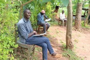 The Water Project: Mutambi Community, Kivumbi Spring -  A Community Member Listening To The Facilitator