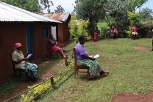 The Water Project: Mutambi Community, Kivumbi Spring -  Community Members Seated In Anticipation
