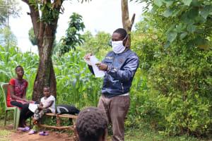 The Water Project: Mutambi Community, Kivumbi Spring -  The Facilitator Demonstrating How To Make A Mask