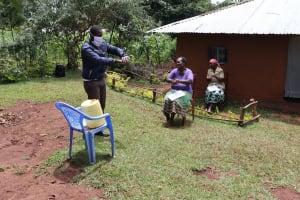 The Water Project: Mutambi Community, Kivumbi Spring -  The Facilitator Demonstrating The Ten Steps Of Handwashing
