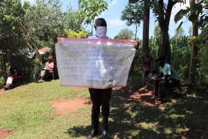 The Water Project: Mutambi Community, Kivumbi Spring -  The Facilitator Holding Up The Reminder Chart