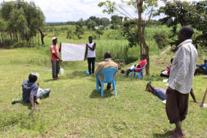 The Water Project: Futsi Fuvili Community, Shikanga Spring -  A Community Member Was Tasked To Read The Points Out Loud