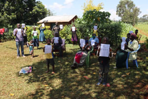 The Water Project: Mtao Community, Tifina Odari Spring -  Participants With Handouts Translated Into Their Local Languages