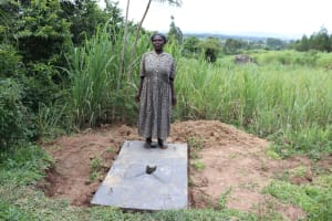 The Water Project: Mahira Community, Litinyi Spring -  A Woman Stands With Her Completed Sanplat
