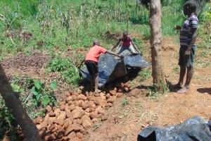The Water Project: Ewamakhumbi Community, Mukungu Spring -  Backfilling With Plastic Tarp