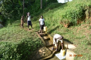 The Water Project: Mungakha Community, Nyanje Spring -  Observing Social Distancing While Fetching Water