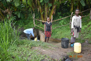The Water Project: Munenga Community, Burudi Spring -  Silas And Other Water Users Observe Social Distancing