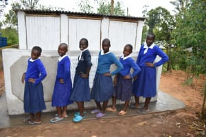 The Water Project: Mutiva Primary School -  Girls Posing In Front Of Their Latrines
