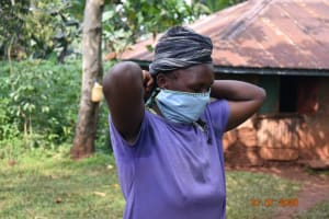 The Water Project: Emulembo Community, Gideon Spring -  Everlyne Puts On Her Mask