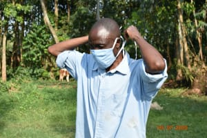 The Water Project: Munenga Community, Burudi Spring -  Silas Puts On His Mask