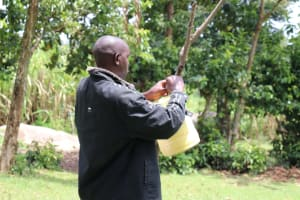 The Water Project: Mahira Community, Litinyi Spring -  Tying Leaky Tin To A Tree