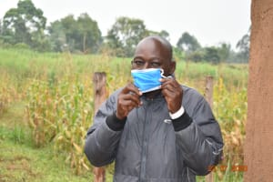 The Water Project: Emukoyani Community, Ombalasi Spring -  Niskson Puts On His Mask