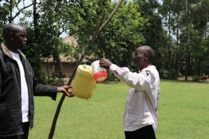 The Water Project: Mahira Community, Litinyi Spring -  Filling Leaky Tin With Water