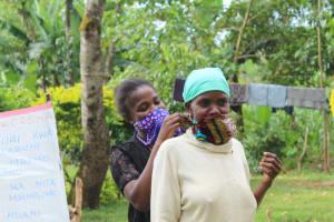 The Water Project: Bukhunyilu Community, Solomon Wangula Spring -  Helping An Elderly Lady Wear Her Mask
