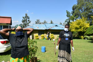 The Water Project: Ivulugulu Community, Ishangwela Spring -  Trying On Mask Made At The Training