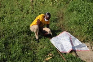 The Water Project: Musango Community, Dawi Spring -  Mr Mutai Mounting The Chart To Support Poles