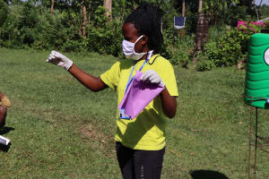 The Water Project: Musango Community, Dawi Spring -  Ms Gladys Showing The Community Members A Simple Way Of Making A Mask