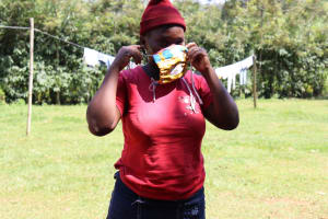The Water Project: Mwituwa Community, Nanjira Spring -  A Woman Trys On A Sample Mask Made At The Training