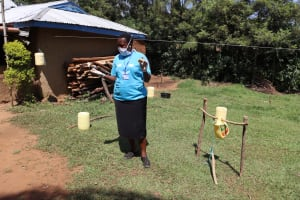 The Water Project: Mwituwa Community, Nanjira Spring -  Facilitator Directing How To Use A Handwashing Station