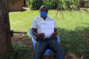 The Water Project: Ataku Community, Ataku Spring -  A Man Shows The Informational Pamphlet On Covid Received At Training