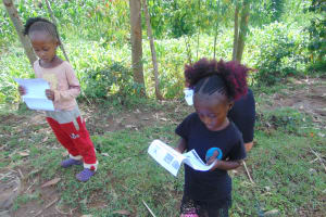 The Water Project: Handidi Community, Chisembe Spring -  Two Girls Reading Through The Documents