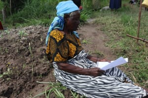 The Water Project: Muyundi Community, Ngalame Spring -  Mama Reading Through The Manual
