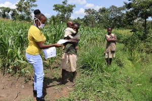 The Water Project: Muyundi Community, Ngalame Spring -  Ms Georgina Handing Out Informational Pamphlets