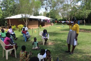 The Water Project: Musango Community, Ndalusia Spring -  Facilitator Illustrating Sneezing Into Elbow